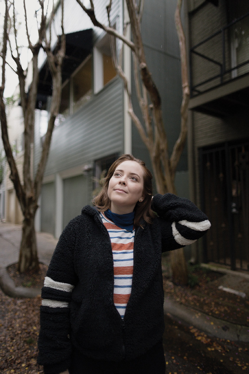a young woman wearing a black sweater and striped t-shirt stands outside by an apartment building looking up toward the sky