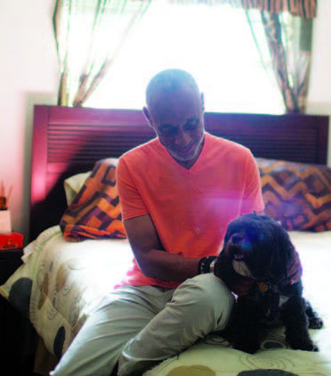 Thomas Wilkins sits in his stylish bedroom holding his small dog, Apollo